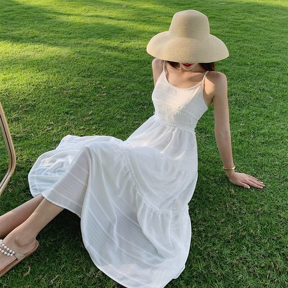 A simple white midi dress with a clean and slightly swooping neckline and spaghetti straps. Great for classics!