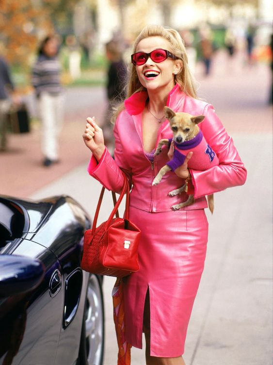 Elle Woods (played by Reese Witherspoon) in the movie 'Legally Blonde'.   When she arrives at Harvard, Elle is wearing a pink two piece set consisting of a cropped jacket and a pencil skirt, with matching pink sunglasses. She's also carrying a red bag that has a red, white, and orange scarf tied to it.