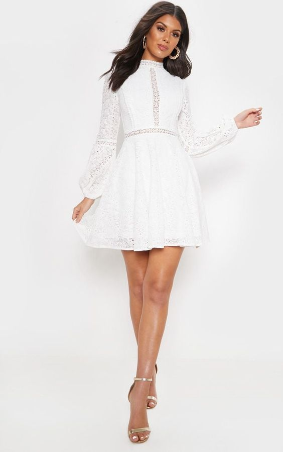 A white mini dress with a mock neckline. The dress has sheer puffed sleeves, and a bit of of sheer lace around the waistline. Great for gamines!