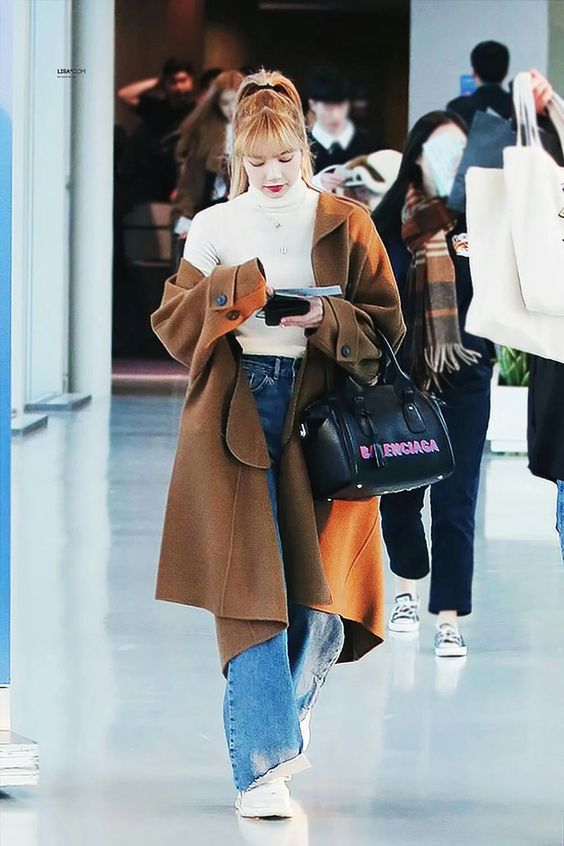 Lisa wearing a long brown wool coat, white turtleneck, flare jeans, white chunky sneakers, and a black Balenciaga bag