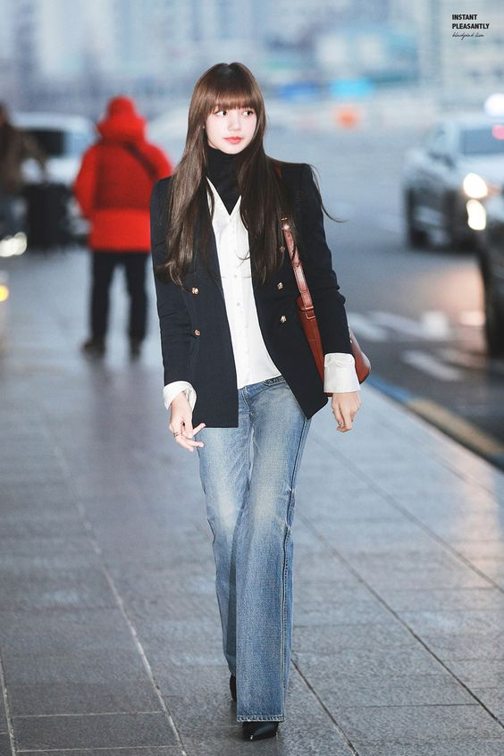 Lisa wearing a black fitted blazer, a white button up shirt, a black turtleneck, lightwash flare jeans, and heels.