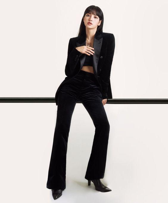 Lisa wearing a black velvet blazer, matching black velvet pants, a black crop top or bandeau, and black pointed heels.