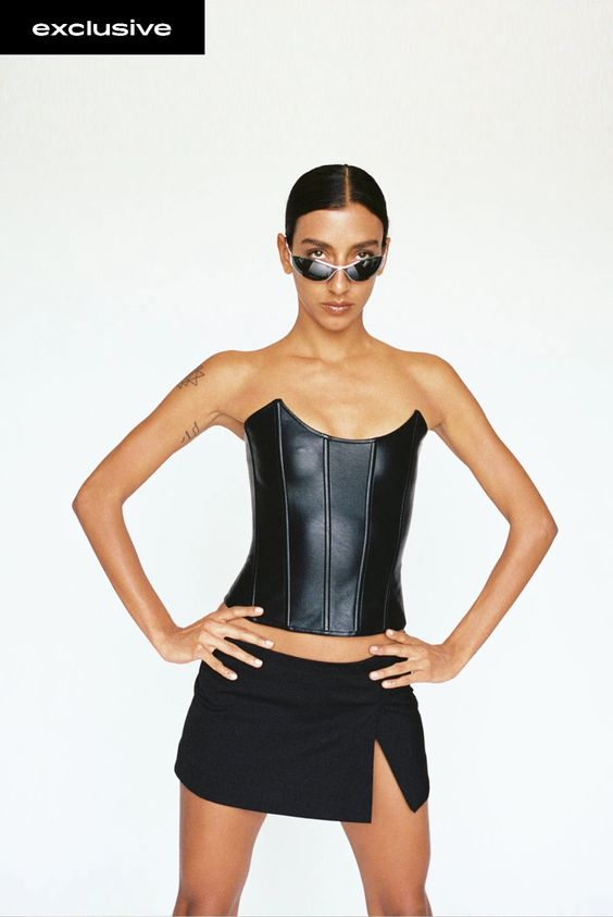 Woman wearing a black micro miniskirt with a faux leather corset and angular black mirrored sunglasses