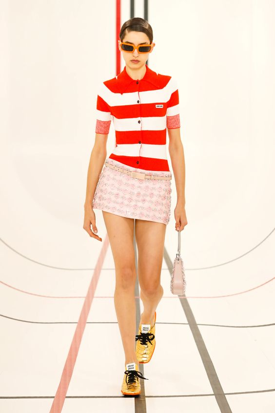 Woman wearing a pink micro miniskirt and a red and white striped polo style shirt