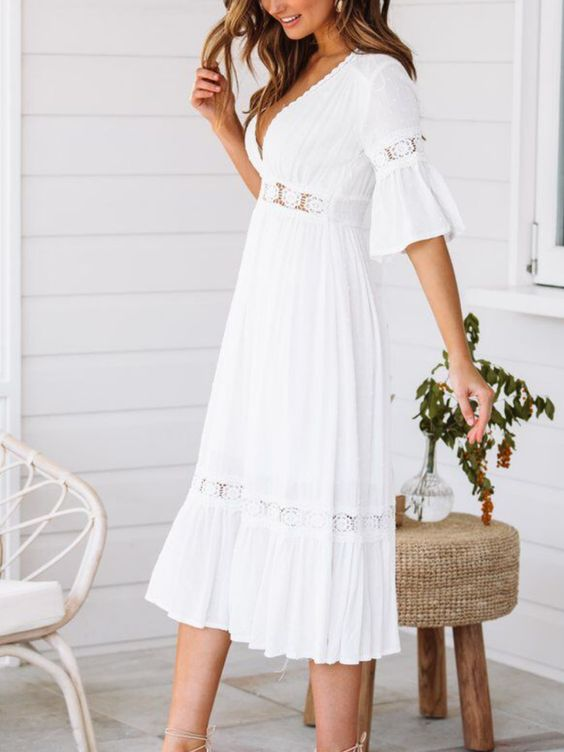 A white midi dress with a v-neckline and lace details. The edges of the hem and neckline are scalloped, and the sleeves have loose ruffling. Great for soft naturals!