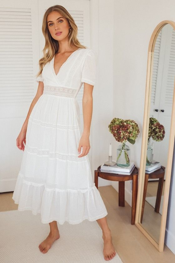 A white midi dress with a v-neckline and a softly fitted bodice, with a long and flowing skirt. Great for naturals!
