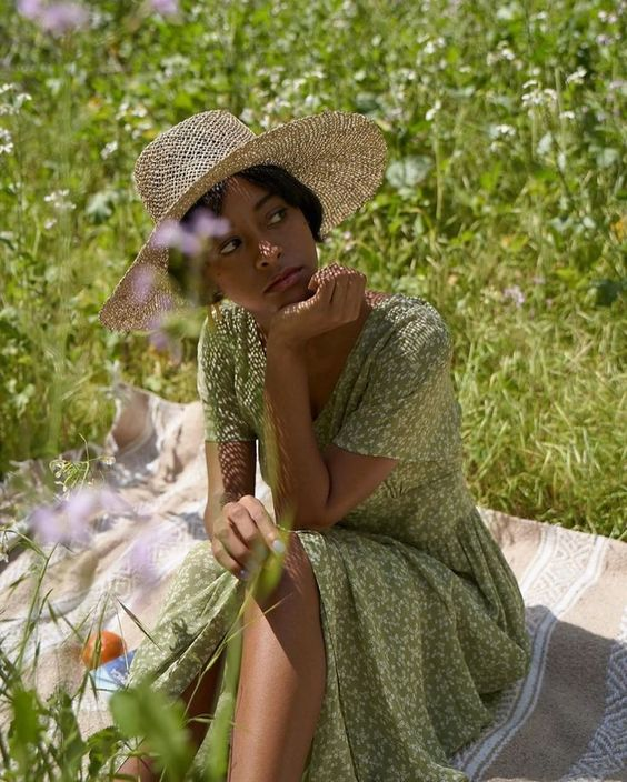Woman wearing a green prairie dress with a straw hat