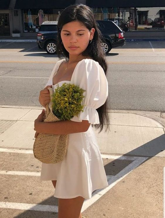 Woman wearing a white mini dress that has large sleeve puffs. She's carrying a knit bag that has flowers in it.