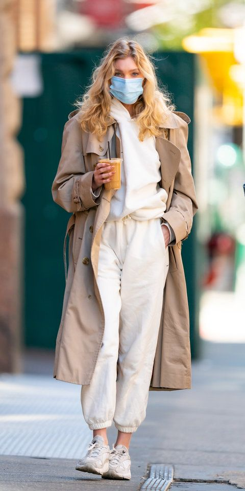 Elsa Hosk wearing a white sweat suit with a trench coat