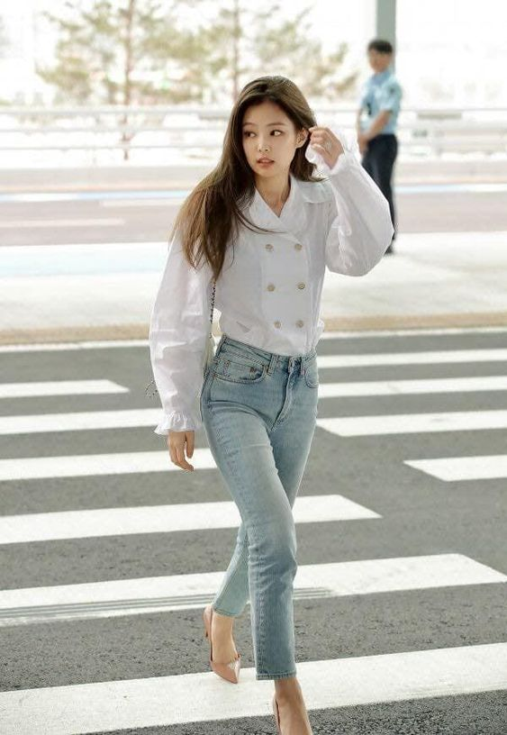 In this outfit Jennie is wearing a white top that looks like a blazer, tucked into lightwash straight leg jeans, and worn with nude stilettos