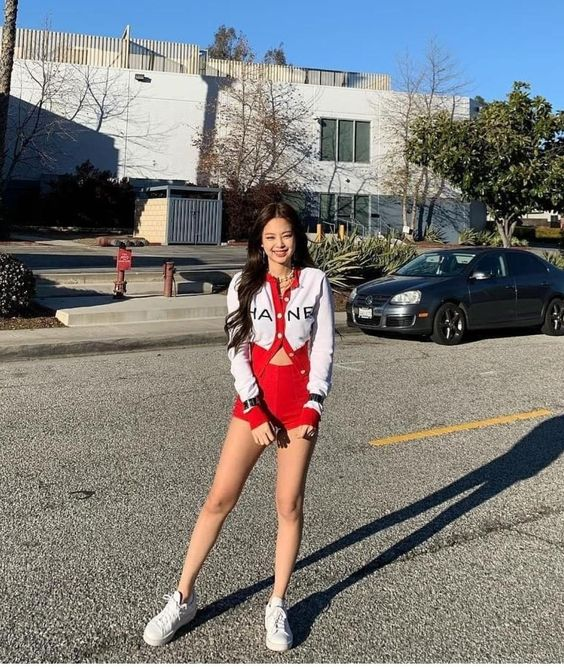 In this outfit Jennie is wearing a white Chanel cardigan with red trim and black stripes, a pair of high waisted red shorts, and white sneakers.