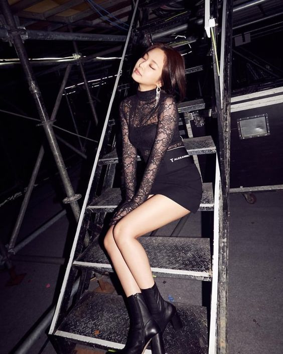 In this outfit Jennie is wearing silver earrings, a black lace top over a black tank top, a black mini skirt, and black ankle boots with chunky heels.